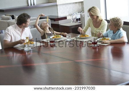 Family Sitting at Table Eating Pasta - stock photo