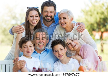 Family sitting at table outdoors, smiling