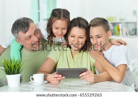 family sitting at table with tablet