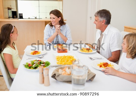 Family sitting at the dinner table together - stock photo