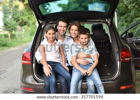 Family sitting in car trunk, ready for vacation - stock photo