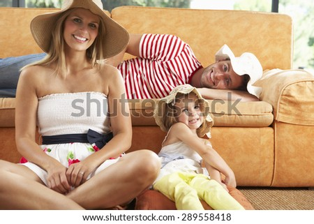 Family Sitting In Front Of Sofa Wearing Straw Hats - stock photo
