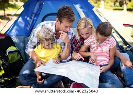 Family sitting in front of tent and looking at map in park