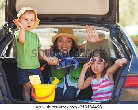 Family sitting in the back of a car smiling to camera and waving. - stock photo
