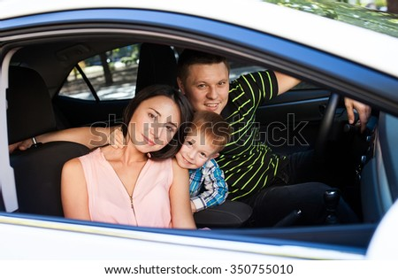 Family sitting in the car looking out windows
