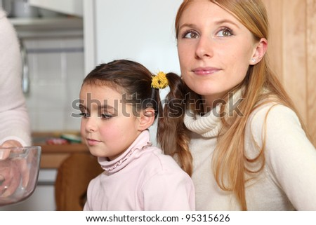 Family sitting in the kitchen - stock photo