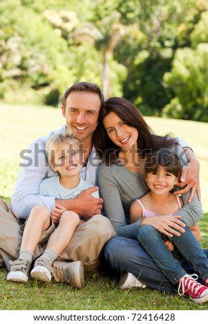Family sitting in the park - stock photo