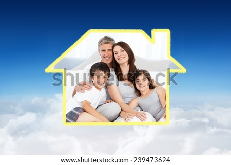 Family sitting on a bed against blue sky over clouds