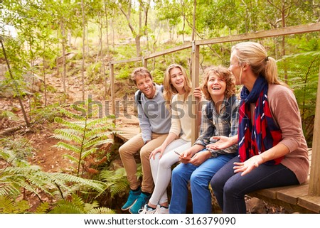 Family sitting on a bridge in a forest talking - stock photo