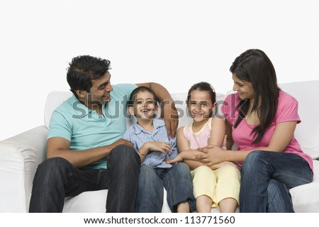 Family sitting on a couch and smiling - stock photo
