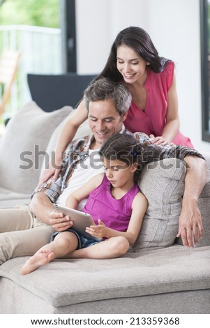 family sitting on a couch looking at a digital tablet - stock photo
