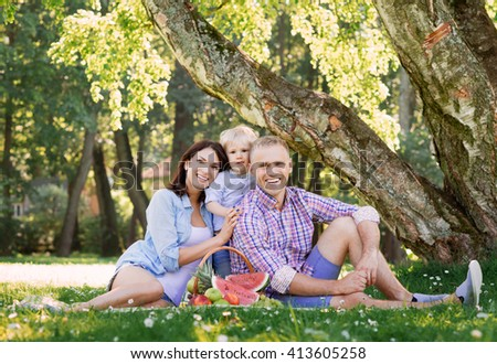 Family sitting on a mat in the park having a healthy picnic with fruits.
