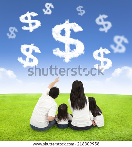 family sitting on a meadow with money of clouds in the blue sky background - stock photo