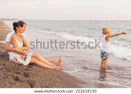 Family sitting on a  sand seashore near sea looking at each other, relaxing on a vacation trip, looking on her husband. copy space - stock photo