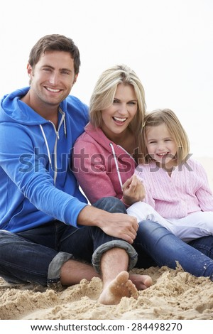 Family Sitting On Beach Together - stock photo