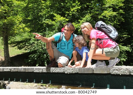 Family sitting on bridge over mountain river - stock photo