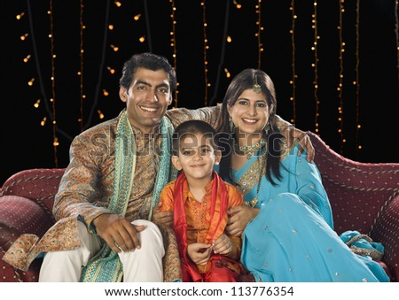 Family sitting on couch and celebrating Diwali festival - stock photo