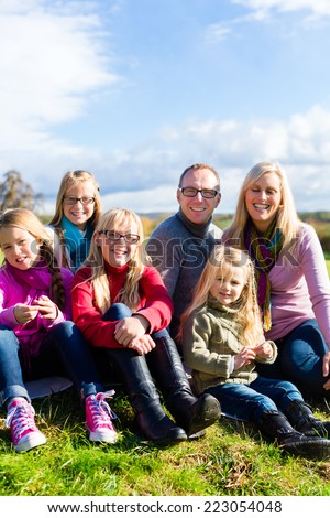Family sitting on fall or autumn meadow