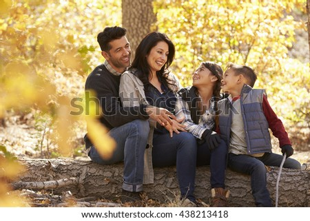 Family sitting on fallen tree in a forest look at each other - stock photo