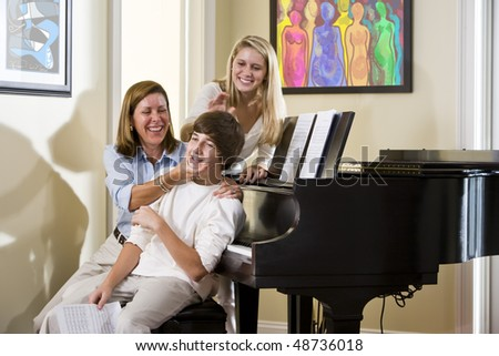 Family sitting on piano bench, mother teasing teenage son