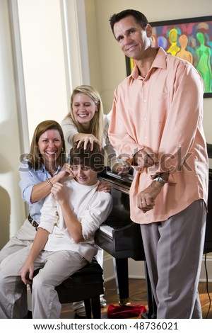 Family sitting on piano bench, mother teasing teenage son - stock photo