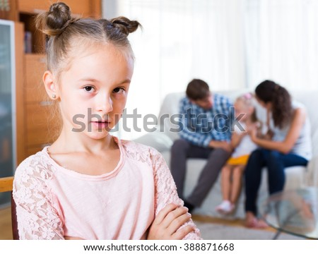 Family sitting on sofa and jealous girl standing apart in domestic  interior - stock photo