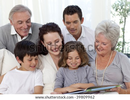 Family sitting on sofa reading a book at home