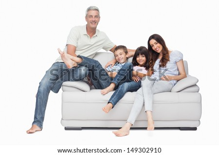 Family sitting on sofa smiling at camera on white background - stock photo