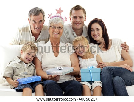 Family sitting on sofa together celebrating grandmother's birthday