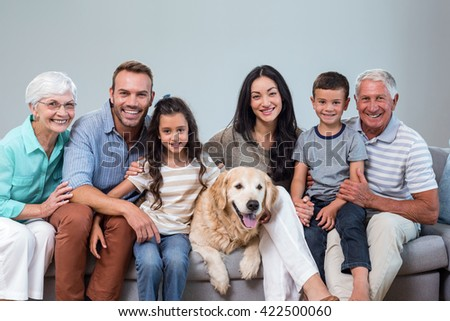 Family sitting on sofa with dog in living room - stock photo