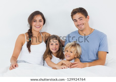 Family sitting on the bed in the bedroom
