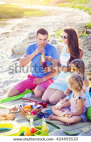 Family sitting on the sand at the beach at the summer picnic. Green bucket with lemonade