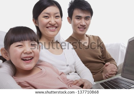 Family sitting on the sofa using laptop, looking at camera, studio shot