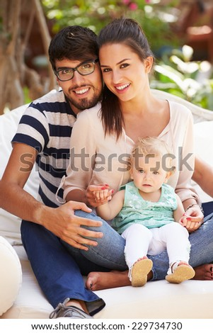 Family Sitting Outdoors In Garden At Home Together - stock photo