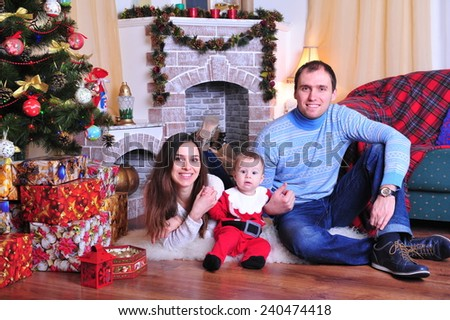 Family sitting together in Christmas interior. Happy family having fun with Christmas presents. Christmas Family Portrait, Mother, father and Son Celebrate Holiday, Opening Present Gift Box  - stock photo