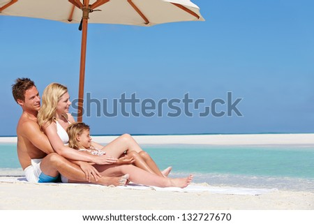 Family Sitting Under Umbrella On Beach Holiday - stock photo