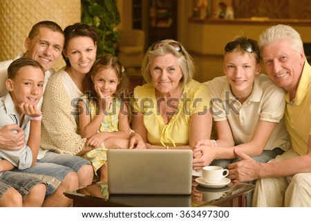 family sitting with laptop - stock photo