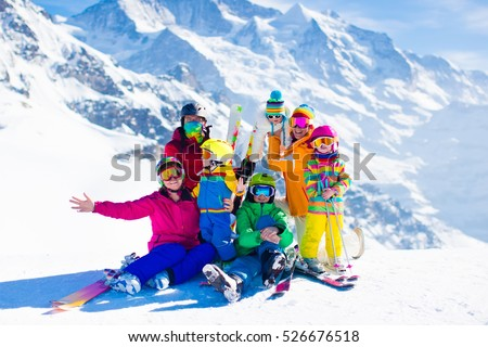 Family ski vacation. Group of skiers in Swiss Alps mountains. Adults and young children, teenager and baby skiing in winter. Parents teach kids alpine downhill skiing. Ski gear and wear, safe helmets.