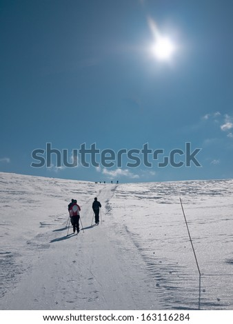 Family skiing uphill a mountainside in a groomed ski track following a group of people visible at the edge of a hill in the norwegian mountains at easter at a day with clear sky and sun in front