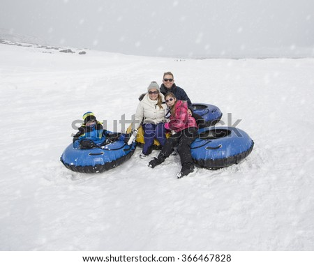 Family Sledding and playing in snow together. Having fun on a snowy day - stock photo