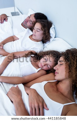Family sleeping together on bed in bedroom - stock photo