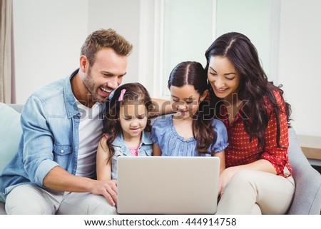 Family smiling and looking in laptop while sitting on sofa at home