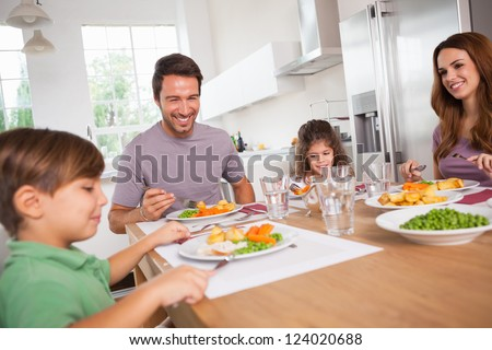 Family smiling around a good meal in kitchen - stock photo
