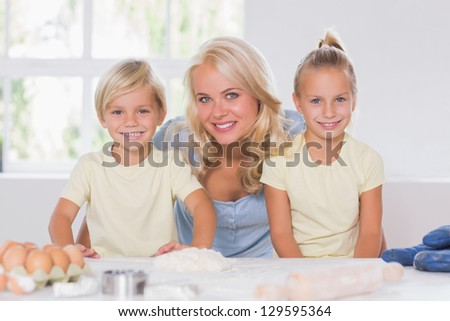 Family smiling at the camera with the baking tools in kitchen