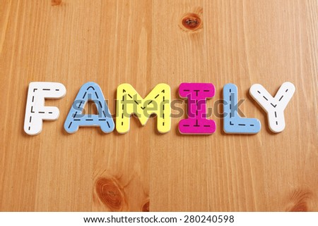 FAMILY, spell by woody puzzle letters with woody background - stock photo