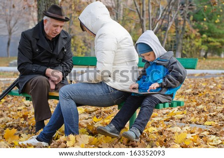 Family spending an autumn day in the park with the elderly grandfather and mother sitting on a bench playing chess while the little boy sits quietly at the end playing on a tablet-pc