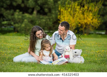 Family spending time together: parents reading book with their daughter