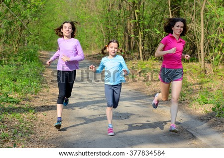 Family sport, happy active mother and kids jogging outdoors, running in forest  - stock photo