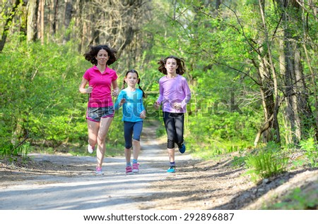 Family sport, happy active mother and two kids jogging outdoors, running in forest