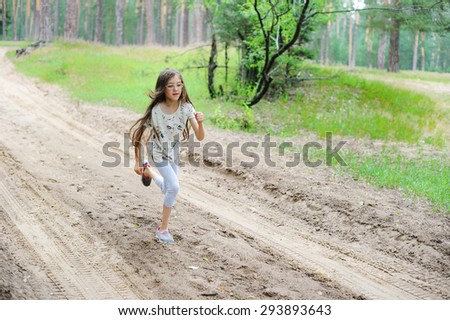 Family sport, happy active school aged brunette girl jogging outdoors, running in forest